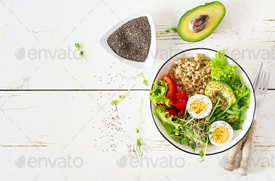 Fresh salad. Breakfast bowl with oatmeal, paprika, avocado, lettuce, microgreens and boiled egg.