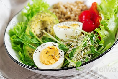 Breakfast bowl with oatmeal, paprika, avocado, lettuce, microgreens and boiled egg.