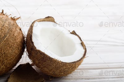 Coconut and shell pieces on white wooden table