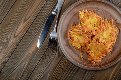 Fresh homemade tasty potato pancakes in clay dish on wooden tabl