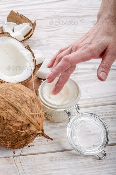Coconut oil on human palm and in airtight glass jar with shell p