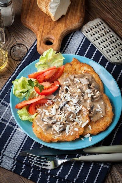 Crispy fried homemade potato pancakes with mushroom sauce.