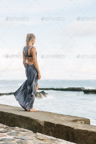 Beautiful lonely in dress at seaside.