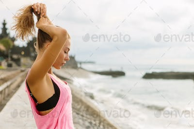 Beautiful girl in sporty outfit on the ocean beach.