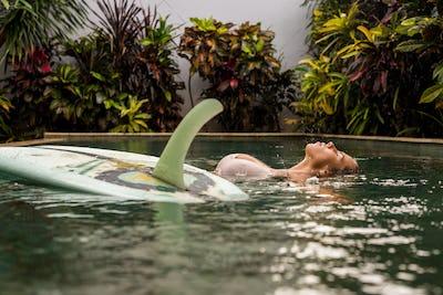 Surfer girl with longboard in pool