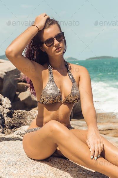 Girl in sexy bikini rest at stone beach.