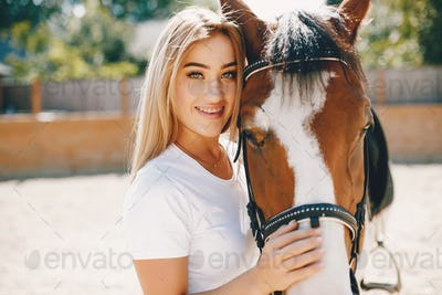 Elegant girl in a farm wiith a horse