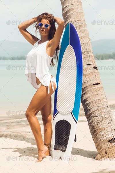 Sexy girl on tropical beach with surf board.