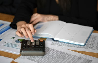 Female makes calculations on a calculator in office.