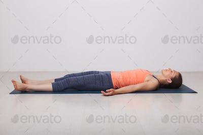 Beautiful sporty fit yogi girl relaxes in yoga asana Savasana