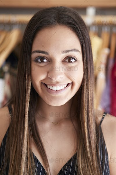 Portrait Of Female Customer Or Owner Standing By Racks Of Clothes In Independent Fashion Store