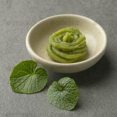 Dish with traditional Japanese horseradish paste and wasabi leav
