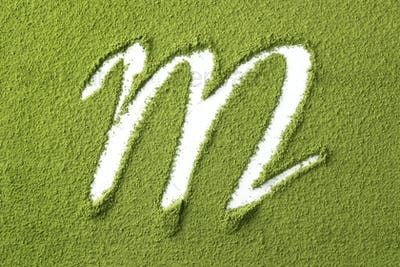 Green Japanese Matcha tea powder full frame and the letter M