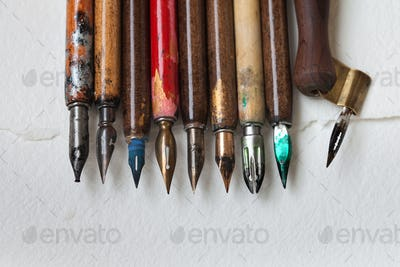 Calligraphic accessories, retro style fountain pen collection. Aged colorful artist pens, textured