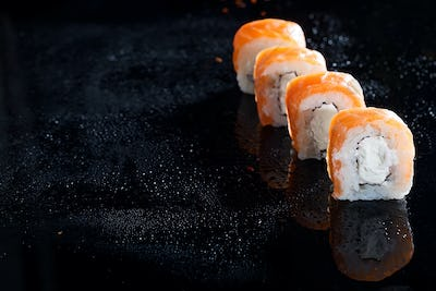 Philadelphia roll classic on black glass background. Japanese sushi food. Copy space