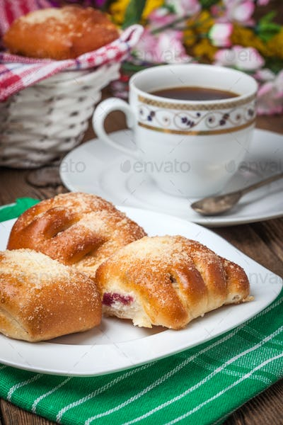 Buns with berries on a wooden table.
