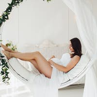 Gorgeous pregnant woman in white gown on designed chair