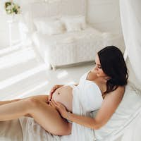 Pregnant woman in white dress lying on bed and resting