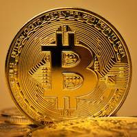 Closeup of shiny gold bitcoin on yellow backgound