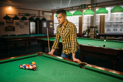Male billiard player, poolroom on background