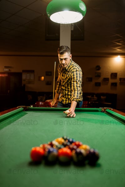 Male billiard player with cue aiming at the table