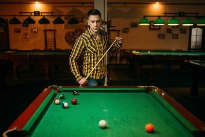 Male billiard player with cue at the table