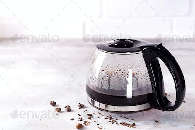 a filled coffee pot with coffee beans against a stone gray background, copy space