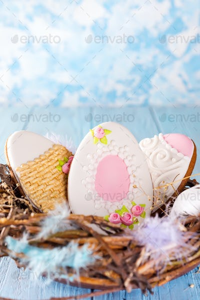 Colorful easter eggs cookies in wooden nest on blue wooden background