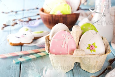 Colorful easter eggs cookies in paper tray on blue wooden background