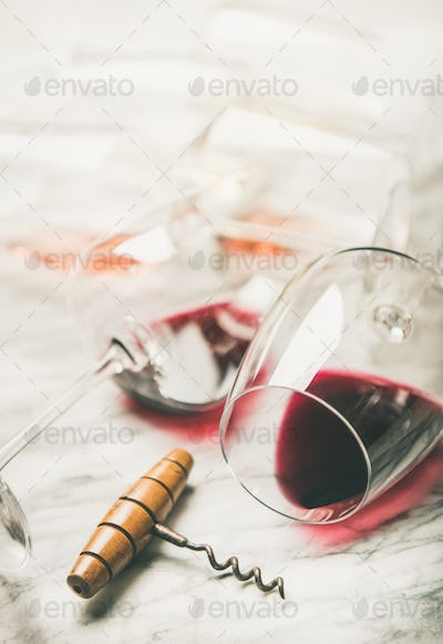Red and rose wine in glasses over grey marble background