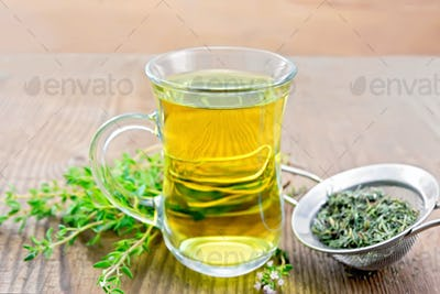 Tea of thyme in mug with strainer on wooden board