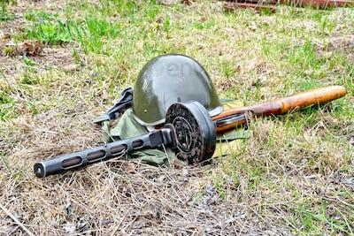 Helmet and submachine gun on ground