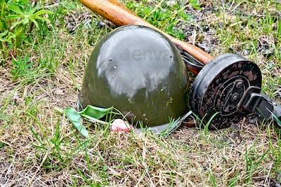 Helmet and submachine gun with tulip on grass