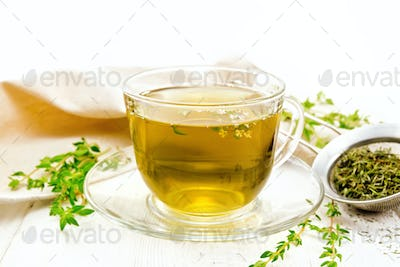 Tea of thyme in cup on table