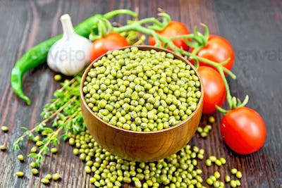 Mung beans  in bowl with vegetables and thyme on dark board