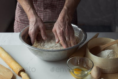 A handful of flour with egg on a rustic kitchen. Against the background of men's hands