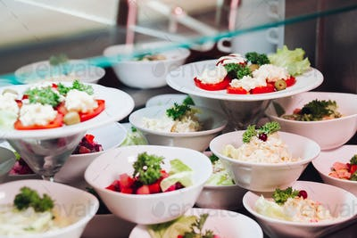 Many round plates with tasty vegetables dish of salads in restaurant
