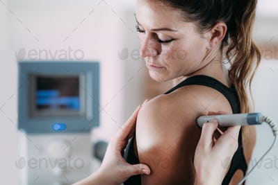 Laser therapy. Physical therapist treating patient's shoulder