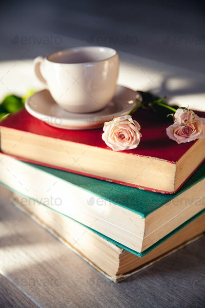 Beautiful bouquet of roses in the sun on the books with a cup