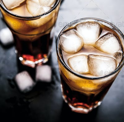 cola with ice on a wooden background. soft drinks