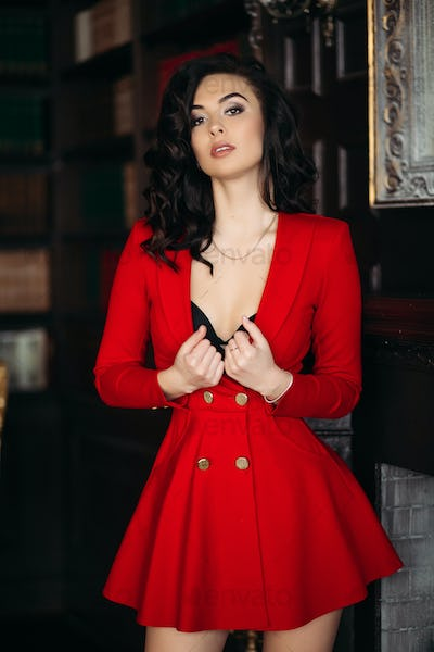 Sexy girl in red dress undresiing touching her chest and undressing