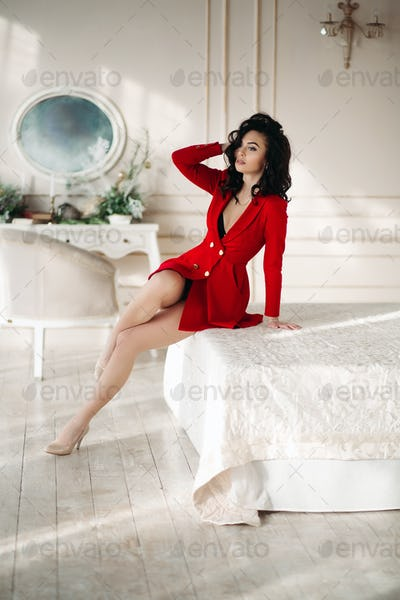 Sexy brunette girl in red blazer seductive posing at bed
