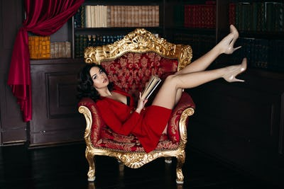 Sexy young brunette lying on big armchair in library