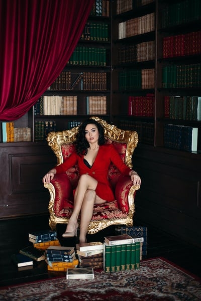 Portrait of brunette in red dress sitting on armchair at library interior