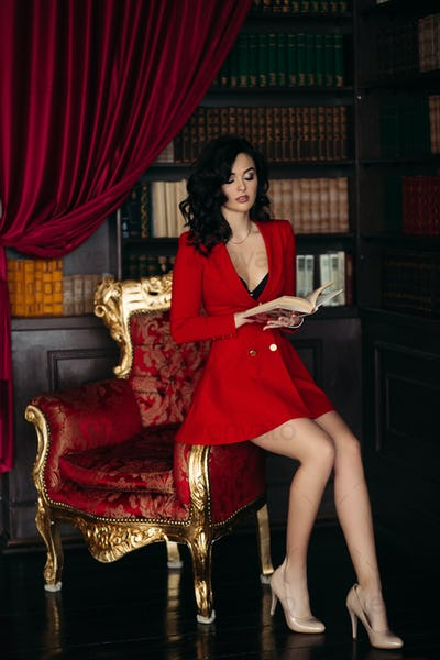 Elegant brunette in red sitting on and holding a book