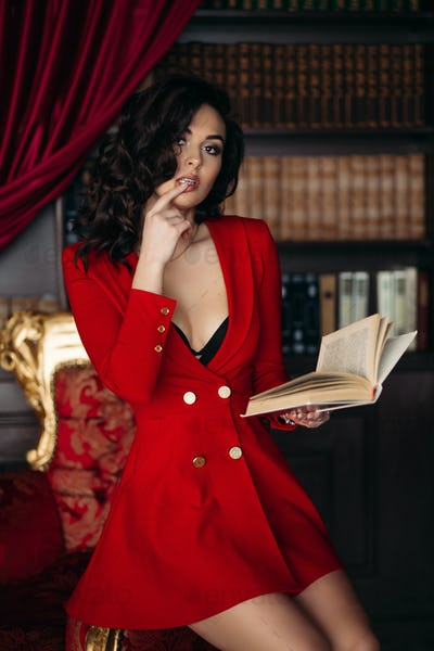 Hot girl in red dress touching her lips holding book in hand