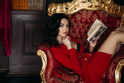 Hot girl in short red dress holding book, lying in library