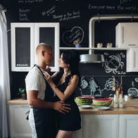 Husband cooking dinner for adorable pregnant wife at home