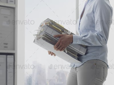 Office worker carrying paperwork in the office