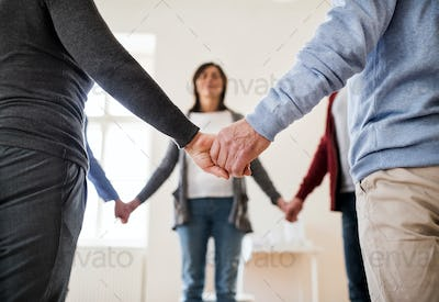 Midsection of people standing in a circle and holding hands during group therapy.